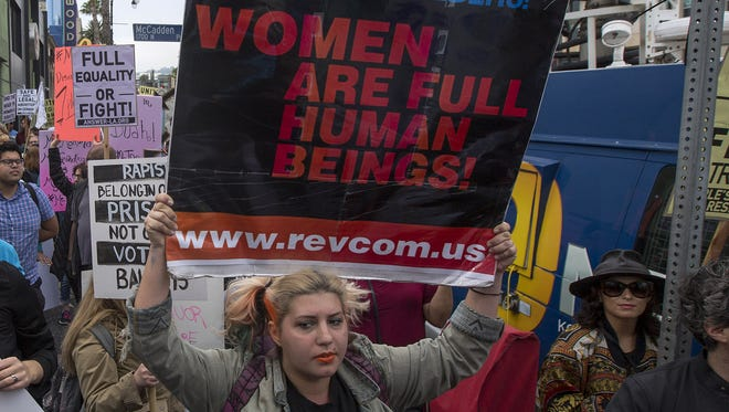 """A protester holds a sign reading """"Women are full human beings!"""" as demonstrators participate in the #MeToo Survivors' March on Nov. 12, 2017, in Los Angeles."""