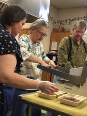 Head Chef Christy Vannoy, left, volunteer Dottie Begman and Meals on Wheels board member Dave Morningstar  far right, prepare meals for elderly and shut ins in Greater Chambersburg area.