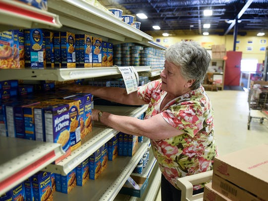 Volunteer Idell Muenzer stocks boxes of macaroni and