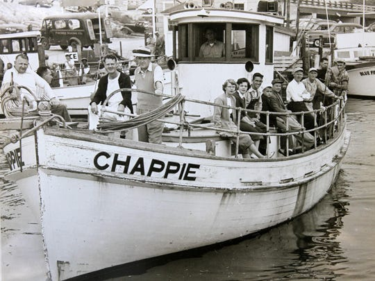 """TANYA BREEN/STAFF PHOTOGRAPHERShawn Shaughnessy displays a photograph, dated approximately 1951, of his father, (third person sitting on right side) Paul, who was the first mate on the party boat Chappie. Shawn Shaughnessy, known as a """"clamdigger,"""" a person born and raised in Point Pleasant, displays a photograph, dated approximately 1951, of his father, (3rd person sitting on right side) Paul, who was the first mate on the party boat named Chappie, in front of the home he was raised in, which was built in 1968 and where his father still resides, in Point Pleasant Beach, NJ Tuesday June 9, 2015. Staff photo Tanya Breen ASB 0609 CLAMMER"""