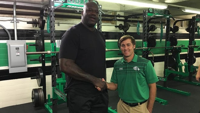 Shaquille O'Neal poses with Lafayette High Coach Rob Poole in the school's new weight room.