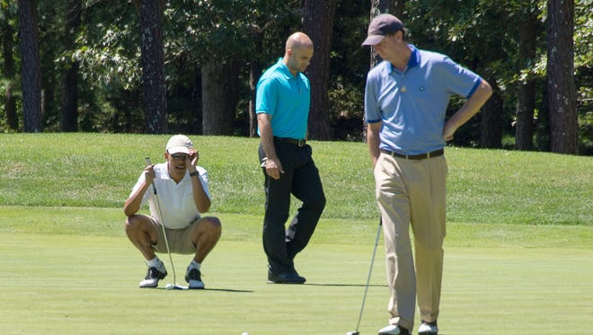 President Obama lines up a putt as White House aides Sam Kass, center, and Marvin Nicholson , right, look on.
