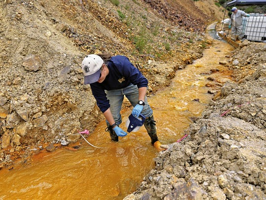 Megan Oller, an assistant engineer associate with Western Solutions Inc., measures water flowing out of Gold King Mine on Aug. 10, 2015.