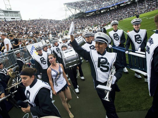 Members of the Penn State Blue Band wave to the audience after their half-time performance Sept. 26 at Beaver Stadium.