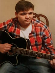 This family photo shows Joseph Livingston of Altoona with one of his guitars. Livingston died on Christmas eve in a weather-related car accident while on his way to spend Christmas with his father in Marshalltown.