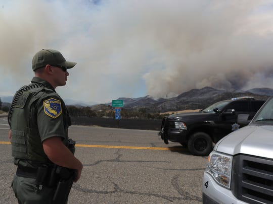 Game Warden Chad Edwards of the California Department of Fish and Wildlife watches smoke from the Klamathon Fire at a checkpoint Friday.