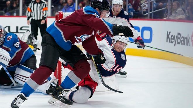 Colorado Avalanche defenseman Cale Makar (8) knocks over Columbus Blue Jackets center Gustav Nyquist (14) during the first period of an NHL hockey game, Saturday, Nov. 9, 2019, in Denver. (AP Photo/Jack Dempsey)