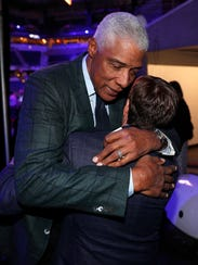 Julius Erving hugs and is greeted by Bob Costas during