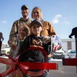 Rachel Chaplin, top right, poses with her family after cutting the ribbon at the opening of Little Bear Peak at Front Range Community College on Friday in Fort Collins.