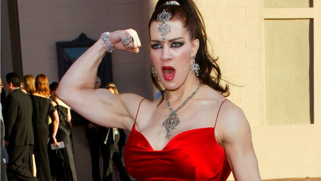 In this Nov. 16, 2003, photo, Joanie Laurer, former pro wrestler known as Chyna, flexes her bicep as she arrives at the 31st annual American Music Awards, in Los Angeles. Chyna, the WWE star who became one of the best known and most popular female professional wrestlers in history in the late 1990s, has died at age 45. Los Angeles County coroner's Lt. Larry Dietz says Chyna, whose real name is Joan Marie Laurer, was found dead in Redondo Beach on Wednesday, April 20, 2016.