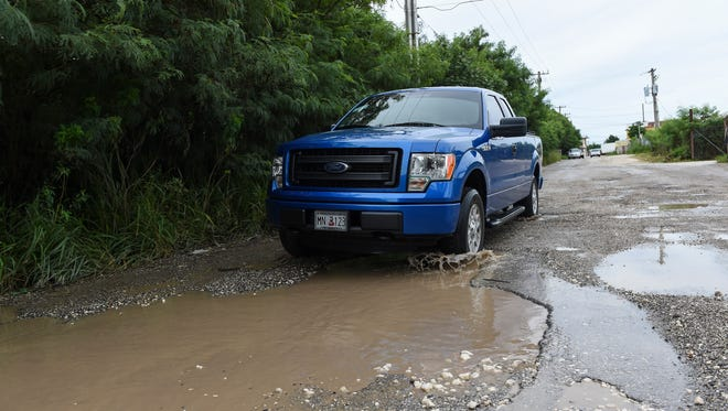 Vehicles approach large, puddled potholes on Harmon Industrial Park Road in Harmon on Oct. 17.