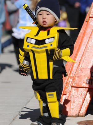 Jayden Yang, 2, dresses in a bumblebee ninja costume while trick-or- treating during Oshkosh's downtown Halloween festival in 2012.