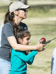 Liz Moreno teaches her daughter Ally Moreno, 7, to cast her line on Saturday, March 24, 2018, during a free fishing clinic at Alumni Pond.