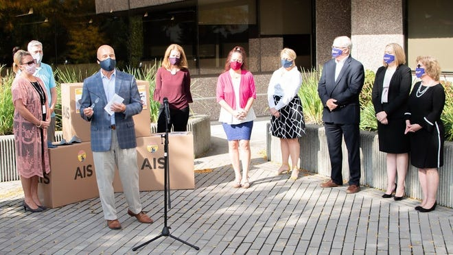 AIS President and CEO Bruce Platzman, third from left, speaks at the Sept. 29 mask donation ceremony outside AIS headquarters.