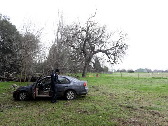 Redding Police officer Kyle Corrigan investigates the scene Monday where a car chase ended in a field off of Green Acres Lane in Redding.