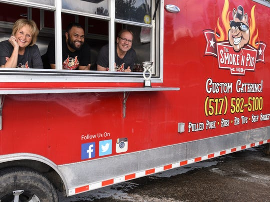"""Mary (left) and Bryan (right) Torok, and son Gabe Jones (middle), AKA the """"Swine Master,"""" co-owners of The Smoke 'N Pig BBQ food truck, pictured Tuesday, March 13, 2018, at 6130 West Saginaw in Lansing."""