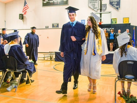 "Graduating Seniors march in to ""Pomp and Circumstance."""