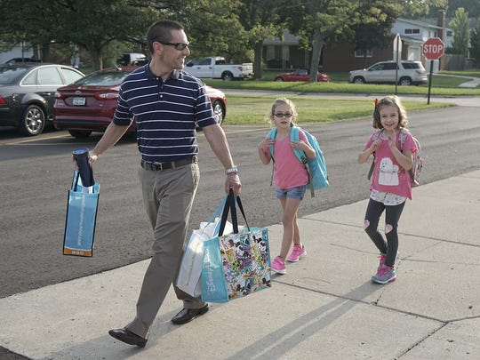 Dad Mark Marry leads the way to the first day of the new school year. Daughters Sarah, third grade, and Emma, first grade, follow pretty close behind.