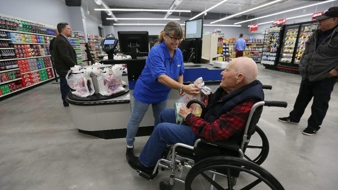 """Lloyd Ratts, of St. John, makes the first purchase from White's Foodliner in St. John at its grand opening in October 2018. Ratts died in 2019, but the grocery store has since caught the attention of the """"NBC Today Show Weekend"""" that came to St. John on Friday to film a segment that will be included in a story on rural grocery stores."""