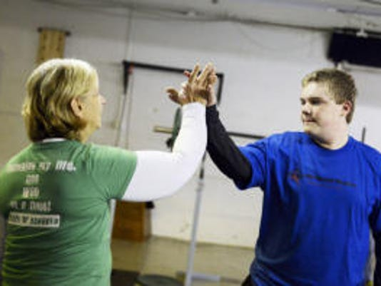 CrossFit coach Sheron Smith, left, high-fives Kasey Keene, 13, during a Special Warriors session in November at CrossFit Hanover. Smith said she created the program because there aren't many fitness outlets for people with special needs. (Kate Penn -- Daily Record/Sunday News)