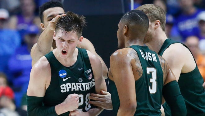 Michigan State's Matt McQuaid, center, celebrates with teammates Kenny Goins, left, and Alvin Ellis III, right, in the first half of the NCAA tournament game Friday in Tulsa, Okla.