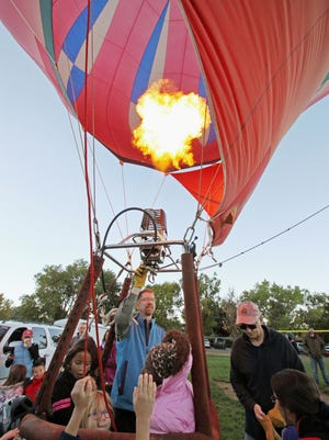 Students surround Albuquerque pilot Steve Adams' basket as he operates the propane burner during the Aloft event at S.Y. Jackson Elementary School, marking the first official event of this year's Albuquerque International Balloon Fiesta in Albuquerque, N.M., Friday, Oct. 3, 2014. The nine-day fiesta gets underway Saturday, Oct. 4, 2014, with a mass ascension of hundreds of balloons at balloon fiesta park.