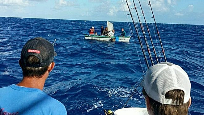 """Capt. Jim Hendrix, left, and Konnor Ross, the son of the other captain for """"Relentless,"""" look over at a small boat they discovered with six Cuban refugees on it over the weekend."""