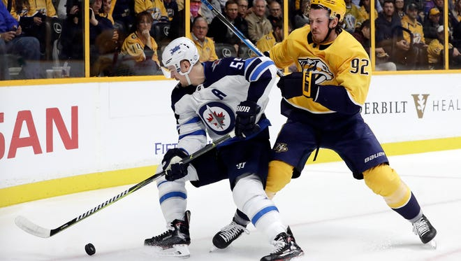 Winnipeg Jets center Mark Scheifele (55) and Nashville Predators center Ryan Johansen (92) battle for the puck in the first period of an NHL hockey game Monday, Nov. 20, 2017, in Nashville, Tenn. (AP Photo/Mark Humphrey)