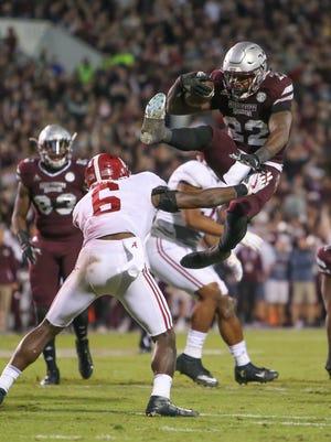 Mississippi State's Aeris Williams (22) hurdles Alabama's Hootie Jones (6) in the red zone Saturday in Starkville.