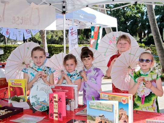 Lower elementary students proudly wear colorful Chinese cheongsams (long robes) holding their traditional parasols with a display of authentic Chinese artifacts and books.