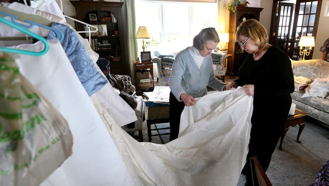 Bernadette Reidy (L) and Josephine Zangi Smith examine a used wedding dress donated to be used to make burial gowns for infants and young children.  The volunteer group supplies area hospitals and hopes to ease the pain of losing a baby.