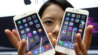 A customer shows off the new Apple iPhone 6 and 6 Plus at a store in Tokyo.