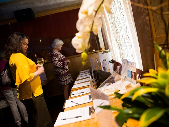 Attendees peruse the items up for silent auction during the NABOR Fire Benefit on Tuesday, May 9, 2017 at Noodles Italian Cafe & Sushi Bar in North Naples. The Naples Area Board of Realtors held the fundraiser in an effort to aid those who lost their home in the Collier County brush fires.