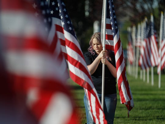 Alyssa Smith prepares to place a flag Friday for the annual Healing Fields display at the Boys & Girls Clubs of Farmington.