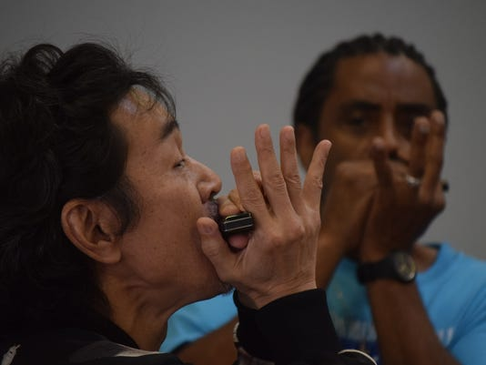"""""""Sweet Harp"""" Kimura of Japan (left) plays harmonica at a harmonica workshop conducted by Kenny Neal (far right) and John Jordan Saturday at Tipitina's in downtown Alexandria. Kimura is a part of the band Nacomi & The Blues Temple which played at the Little Walter Festival."""