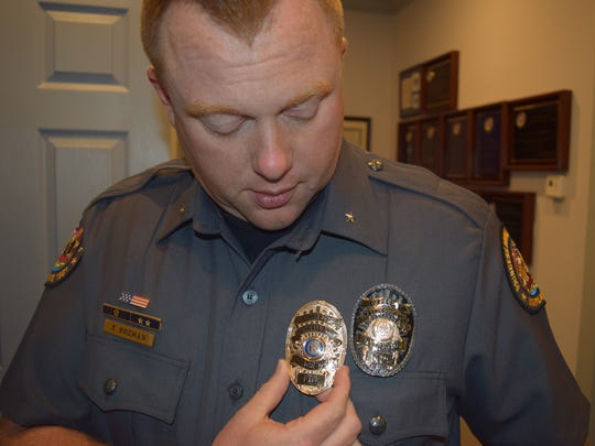Tim Bozman, Princess Anne police chief, holds up an old gold police department badge against the agency's new badge. The department changed to a black badge when they changed uniforms this spring.
