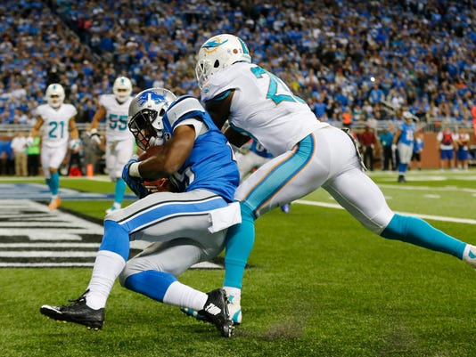Detroit Lions running back Theo Riddick (25), defended by Miami Dolphins strong safety Reshad Jones (20), scores on an 11-yard reception during the second half of an NFL football game in Detroit, Sunday, Nov. 9, 2014. (AP Photo/Paul Sancya)