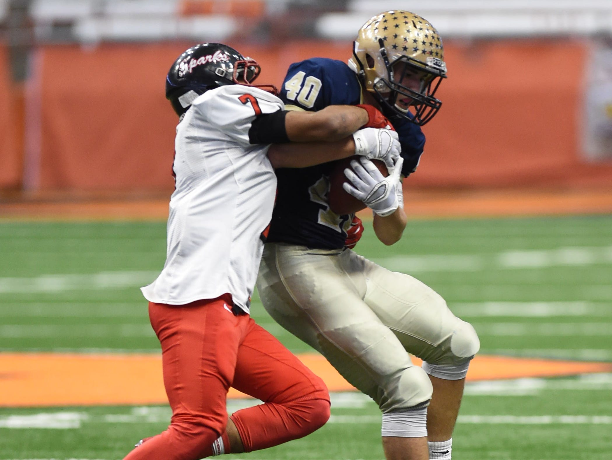 Lourdes' Billy Wagner gets tackled by South Park's Tyree Brown during the New York State Championship final in Syracuse on Friday.