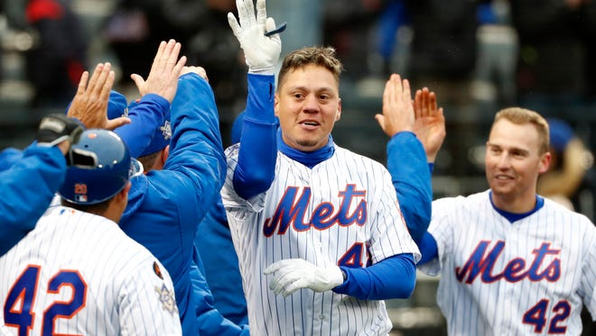 New York Mets Wilmer Flores, center, and the Mets Brandon Nimmo celebrate with teammates after Flores hit a walk-off, solo, home run in the ninth inning of a baseball game against the Milwaukee Brewers, Sunday, April 15, 2018, in New York.
