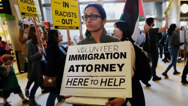 A woman offers legal services at the customs arrival area as demonstrators opposed to President Donald Trump's executive orders barring entry to the U.S. by Muslims from certain countries march behind at the Tom Bradley International Terminal at Los Angeles International Airport on Saturday.