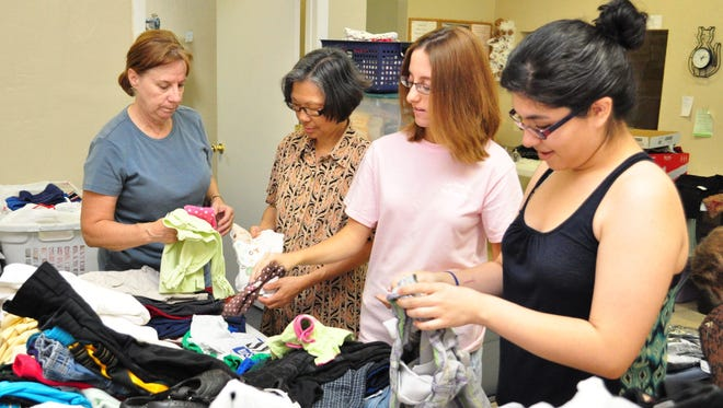 Volunteers (from left) Margaret Rosenfield, Sally Zagala, Michelle Simo and Ixchel Verdugo, sort clothes at The Clothes Cabin in Chandler.