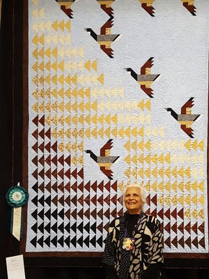 Vijay Bhalla poses with her award-winning quilt, Naturally Free and Thriving