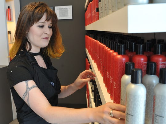 Newly opened Fantastic Sams Cut and Color Hair Salon manager, Courtney Williams arranges hair products on May 11. Store owner Shane Ballard said the salon will offer a full menu of services such as haircuts, color, styling and facial waxing.