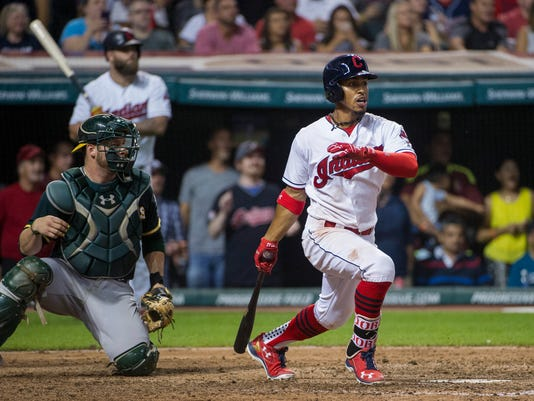 Cleveland Indians Francisco Lindor watches his sacrifice fly off Oakland Athletics reliever Ryan Dull, next to Athletics catcher Stephen Vogt during the seventh inning of a baseball game in Cleveland, Friday, July 29, 2016. The Indians won 5-3. (AP Photo/Phil Long)
