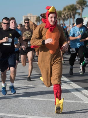 Eric Owens, center, leads the pack of runners out of the starting gate during the 7th annual Pensacola Beach Turkey Trot Thanksgiving morning, Nov. 23, 2017.