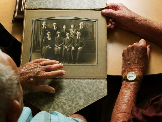 Jack Kaslikowski, 97, left, and brother Walter, 95, reminisce over family photographs recently at the Douglas T. Jacobson State Veterans Home in Port Charlotte, Florida. The brothers served in World War II together.