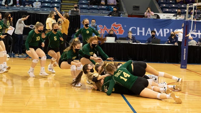 SMCC players swarm off the bench to join the celebration after the Kestrels beat Schoolcraft in the Division 3 state finals Saturday. The Kestrels repeated as Division 3 state champion with a three-set win over Schoolcraft in the finals.