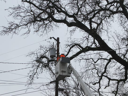 A worker from Redding Electric Utility cuts the power