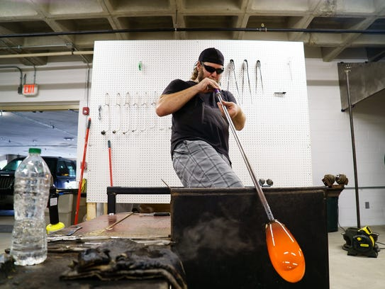 Glass blower Jesse Ahrendsen of Des Moines, works on
