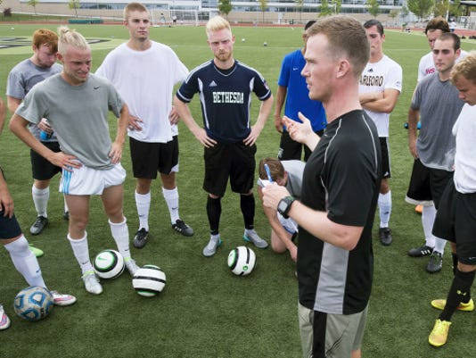 First-year York College coach Evan Scheffey talks to the men's soccer team during Wednesday's practice at York College. Scheffey was a team captain for three of his four years as a Spartan, and now he takes the reins from longtime coach Mark Ludwig.